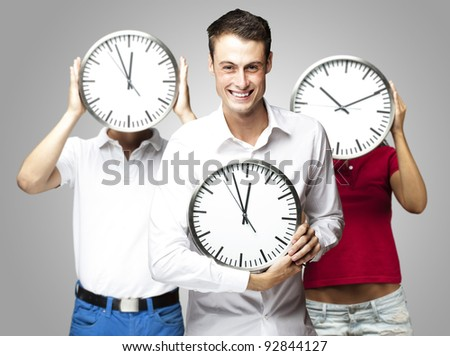 group of young students holding clock against a grey background - stock photo