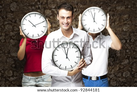 group of young students holding clock against a vintage wall - stock photo