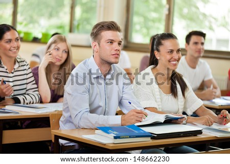Group of young students in classroom listening a lecturer - stock photo