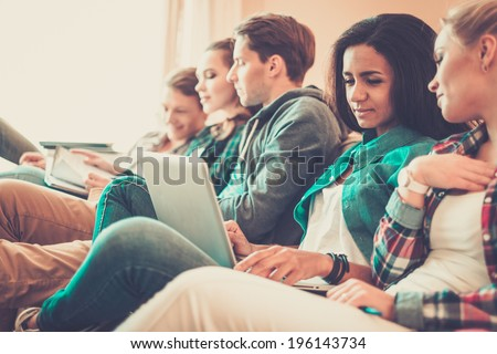 Group of young students preparing for exams in apartment interior - stock photo