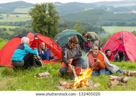 Group of young students spending weekend together in tents campfire - stock photo