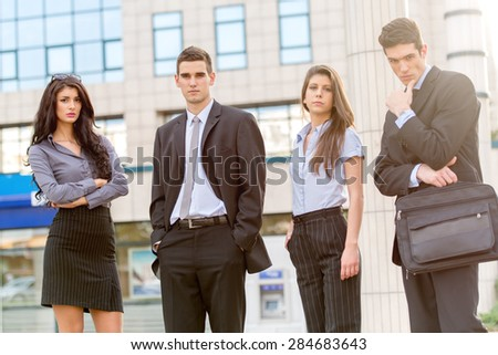 Group of young successful business people standing in front of office building dressed in suits. With a serious expression on their faces looking at the camera.