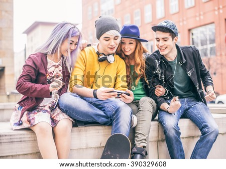 Group of young teens playing videogames outdoors - Cool teenagers hanging out in a university campus - stock photo
