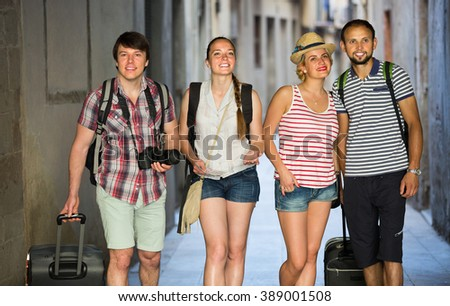 Group of young travelers walking through the city with travel bags. Selective focus - stock photo