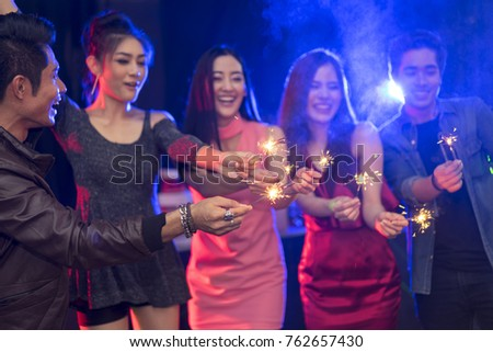 group of young women and boy friend celebrating new years eve at the pub. Group of female friends with sparklers partying in nightclub,focus point sparklers.