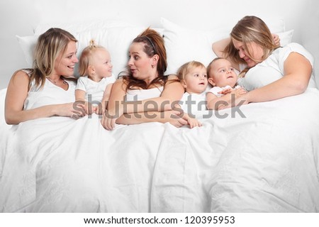Group of young women and her children talking in the bed. Motherhood concept.