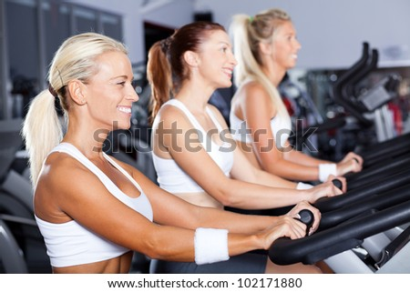 group of young women cycling in gym - stock photo