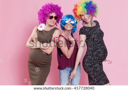 Group of young women disguised for a party, with candies, balloons and wigs.