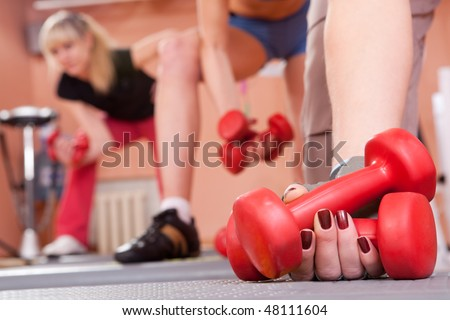 group of young women exercising with red dumbbells - stock photo