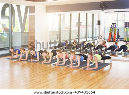 Group of young women in fitness class. Group of people making exercises. Girls do plank for abs exercise. Healthy lifestyle, training, sport, gym studio. Sporty girls in fitness club, aerobics. - stock photo