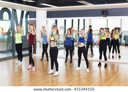 Group of young women in fitness club making exercises with dumbbells. Healthy lifestyle, slim sporty girls at aerobics training. - stock photo