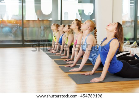 Group of young women in yoga class making exercises. Girls do back stretching. Healthy lifestyle, gymnastics or yoga studio in fitness club. - stock photo