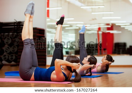 Group of young women working out and strengthening their abs at a gym - stock photo