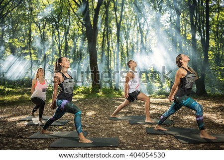 Group of youngsters keep in shape exercising in sunlight woods  - stock photo