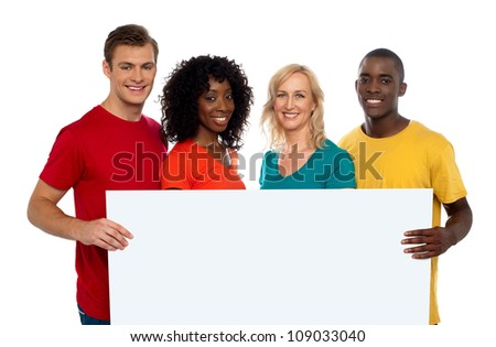 Group of youth displaying blank advertise board and smiling at camera - stock photo