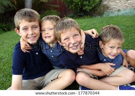Group on young boys sitting in grass - stock photo