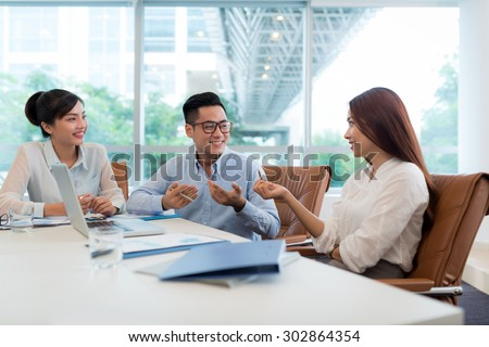 Group on young Vietnamese colleagues discussing business ideas at the meeting - stock photo