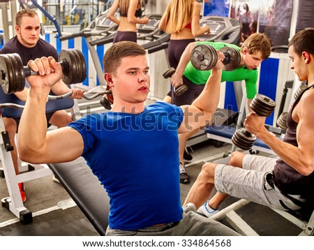 Group people and man in blue clothing working his arms and back at gym. He lying on bench and lifting barbell. - stock photo