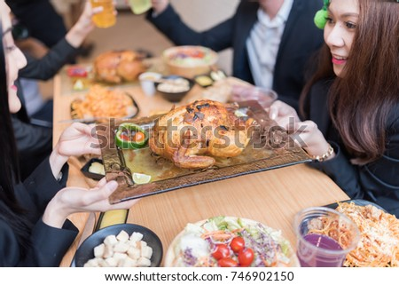 Group people cerebration at restaurant while hiding Big Chicken