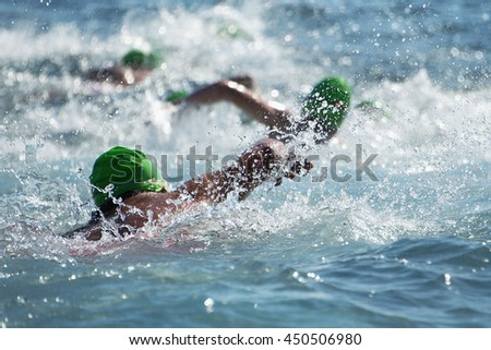 Group people in wetsuit swimming at triathlon - stock photo