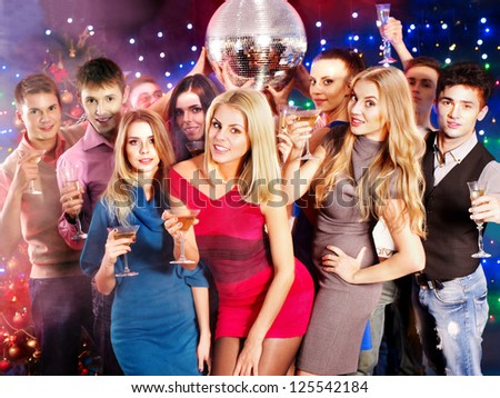 Group people with  champagne dancing at party. Disco ball.