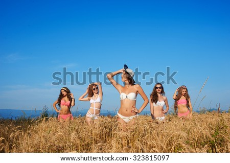 Group photo of charming young girls in bikinis, beautiful sexy models, they smile, posing in wheat field on a background of blue sky.