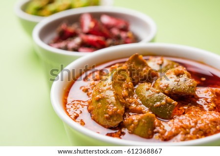 group photo of indian traditional  Mango pickle / aam ka achar, hari mirch achar / green chilli pickle, red chilli pickle / lal mirch ka achar, served in 3 white bowls, selective focus