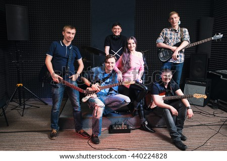 Group photo of student music band. Smiling at camera male musicians and woman vocalist. Music band members posing on stage with their musical instruments. large group of people - stock photo
