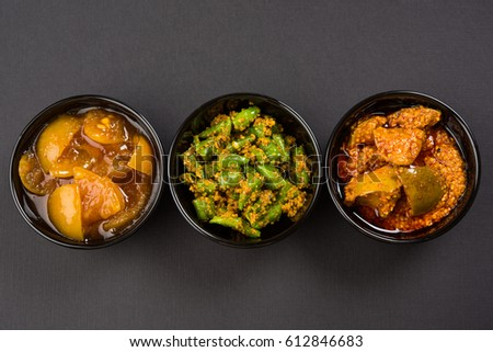 Group photograph of indian pickles like mango pickle , lemon pickle and green chilli pickle, sarved in black ceramic bowl, selective focus