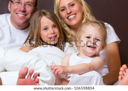 Group picture of a young family, father, mother and children in bedroom - stock photo