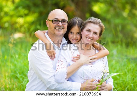 Group Portrait happy smiling family with one child outdoors nature on sunny summer day, park forest. Children parents, grandparents. Positive human emotion, facial expression, feeling, life perception