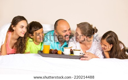 Group portrait looking happy smiling joyful family, mother, father, daughters, son having breakfast in bed, surprise on mom day. Positive human emotions, face expressions, feelings, life perception. - stock photo