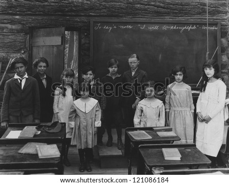 Group portrait of children standing in classroom - stock photo