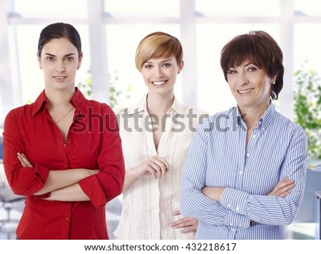 Group portrait of confident casual female caucasian business office workers. Smiling, arms crossed, looking at camera.