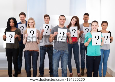 Group portrait of confident college students holding question mark signs in classroom - stock photo