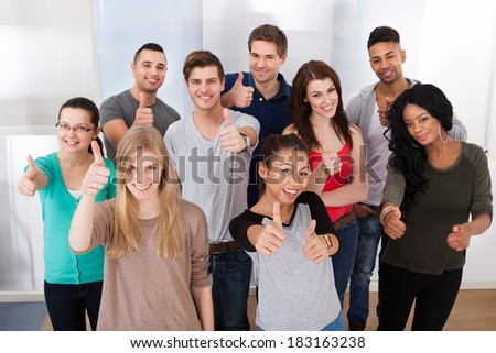 Group portrait of confident multiethnic university students gesturing thumbs up in classroom