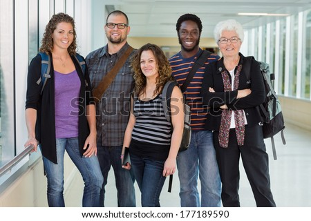 Group portrait of confident multiethnic university students standing in corridor with professor - stock photo