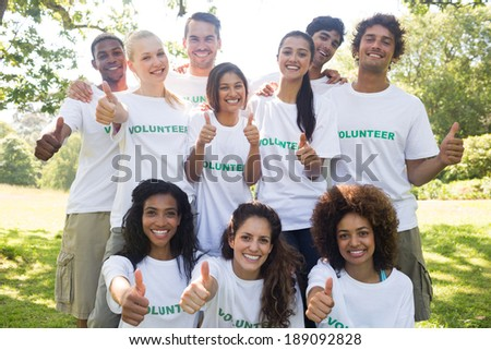 Group portrait of confident volunteers gesturing thumbs up in park