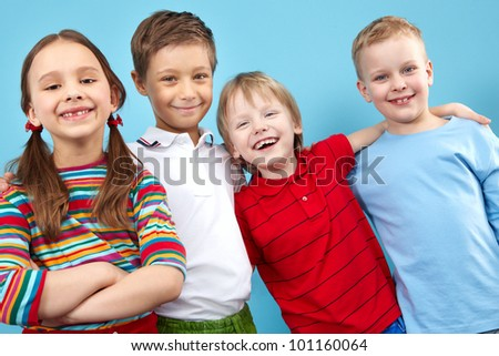 Group portrait of four smiling friends hugging - stock photo