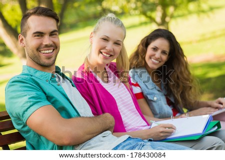 Group portrait of happy college friends sitting on bench at the campus - stock photo