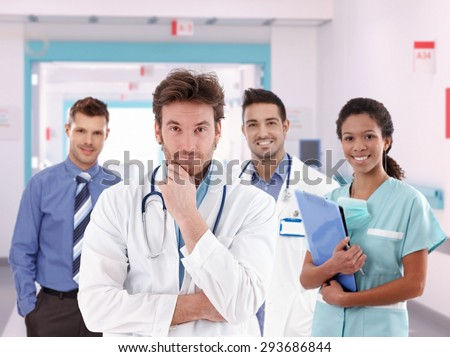 Group portrait of happy doctors at hospital hallway. Handsome man, standing, smiling, looking at camera, wearing lab coat and stethoscope.