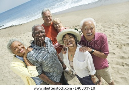Group portrait of happy multiethnic couples smiling on the beach - stock photo