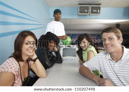 Group portrait of happy multiethnic friends at bowling alley - stock photo