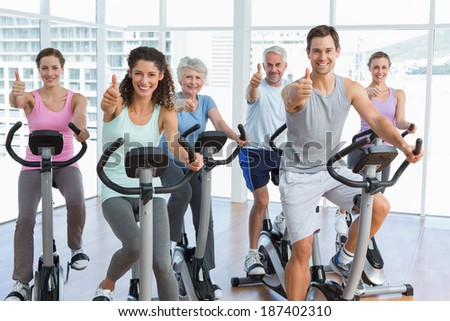 Group portrait of happy people working out at bike class while gesturing thumbs up in gym