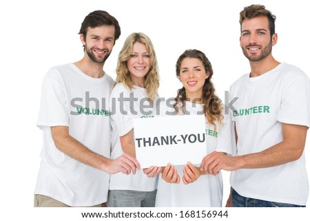Group portrait of happy volunteers holding 'thank you' board over white background - stock photo