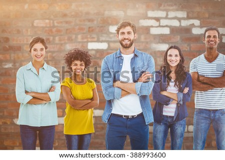 Group portrait of happy young colleagues against brick wall - stock photo