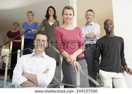 Group portrait of multiethnic business people standing in office - stock photo