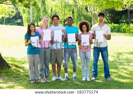 Group portrait of multiethnic friends holding blank papers on campus
