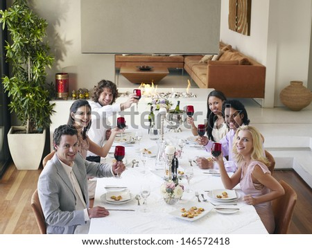 Group portrait of multiethnic friends toasting wineglasses at dinner party - stock photo