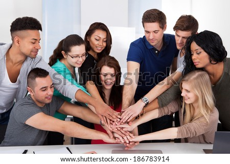 Group portrait of multiethnic university students stacking hands at desk in classroom